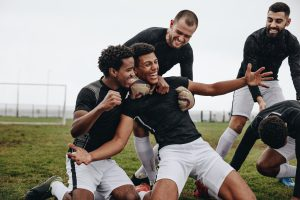 Football players celebrating success on the field. Happy footballer sitting on his knees with open arms after scoring a goal being cheered by his teammates.