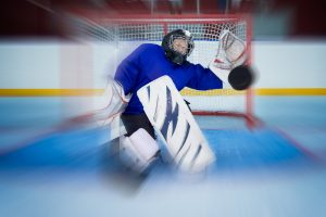 Young goalkeeper catching a  flying puck in knee position. Zoom blur